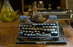 The Old typewriter on a dusty table with bottles Stock Photography