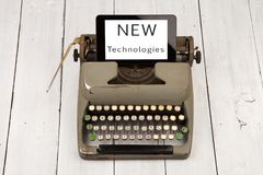 Old typewriter and new tablet pc with words & x22;NEW Technologies& x22;. Concept of technology progress - old typewriter and new tablet pc with words & Royalty Free Stock Photo