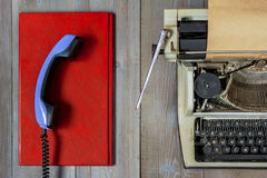 Old typewriter with paper. Fragment of an old typewriter with paper and a handset on a red folder Stock Image