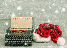 Old typewriter red hat Merry Christmas Wish List. Old typewriter with red hat and sample text Wish List. Retro style picture with falling snow effect Stock Photography