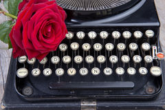 Old typewriter with a red rose Royalty Free Stock Photography