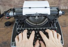 Old typewriter from seventies with paper and copy space. Two hands are typing Royalty Free Stock Image