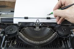 Old typewriter from seventies with paper and copy space. With writing hand.  Royalty Free Stock Photography