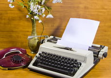 Old typewriter, telephone and ancient vase with camomiles Royalty Free Stock Images