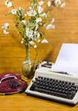 Old typewriter, telephone and ancient vase with camomiles Stock Image
