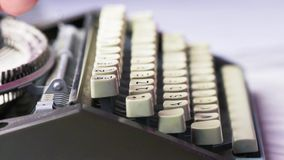 Old typewriter typing. Vintage typewriter being used by male hands seen from the side, using only index fingers pecking keys stock footage