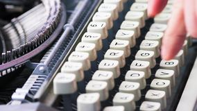 Old typewriter typing. Vintage typewriter being used by male hands seen from the side, using only index fingers pecking keys stock video footage