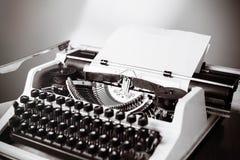 Old typewriter on wooden table. Vintage style tinted photo. Stock Photo