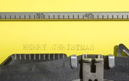 Old typewriter with yellow paper Merry Christmas. Old typewriter with yellow paper with a text Merry Christmas stock photos