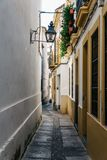 Old typical street in the jewry of Cordoba. Old typical narrow street in the jewish quarter of Cordoba with old buildings with white walls decorated with Stock Photo