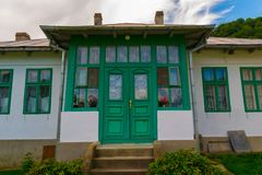 Old typical romanian house facade with green painted wood doors and windows. Old typical romanian house facade with green painted wood doors and windows stock photo