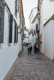 Old typical street in the jewry of Cordoba. Cordoba, Spain - April 10, 2017: Old typical street in the jewish quarter of Cordoba with white walls Royalty Free Stock Photos