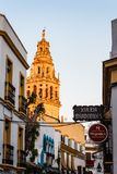 Old typical street in the jewry of Cordoba. Cordoba, Spain - April 11, 2017: Old typical street in the jewry of Cordoba with restaurants and the tower of Great Stock Photo