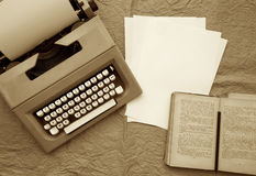 Old typing machine, white sheets of paper,old book on an old paper surface. Royalty Free Stock Photos