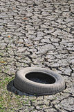 Old tyre. In a dry river. Environmental and ecology problem Stock Photography