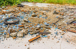 An old tyre in a broken glass zone. Image of An old tyre in a broken glass zone for background usage Stock Image