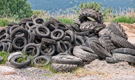 Old tyres- aka tires - in landscape royalty free stock photography