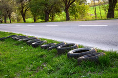 Old tyres next to the empty road Royalty Free Stock Image