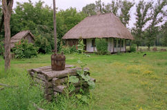 Old Ukrainian house and a well. Old Ukrainian well and house landscape stock image