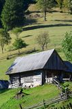 The old Ukrainian hut with a slate roof and a wooden fence in a green fiel. D Stock Photography