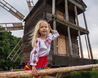 Old ukrainian mill and little girl. Little ukrainian girl smiling on the hedge near old wooden mill stock images