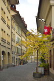 Old Unesco city of Bern with Switzerland and Bern flag. Switzerland. Autumn view of small street with yellow tree from old Unesco city of Bern. Switzerland and Stock Image