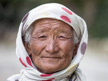 Old unidentified local woman sitting outdoor in Leh. Stock Photos