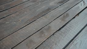 Old unpainted boards in the rain. The camera is moving. Raindrops crashing on wood flooring. April rain. Close-up. Nostalgic mood.  stock footage