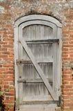 Old unpainted wooden door in brick wall Stock Photo