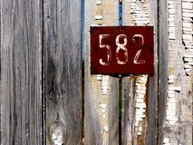 Old unpainted wooden fence. Number 582 is on the fence. Russian vintage. Beautiful old boards. Decor for design style shabby chic. royalty free stock photography