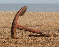 A rusty anchor on Aldeburgh beach. An old and unused  rusty anchor standing upright on the shingle at Aldeburgh in Suffolk Royalty Free Stock Images