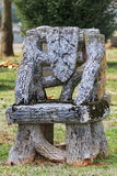 Old unusual empty chair tombstone tree trunks Royalty Free Stock Photo