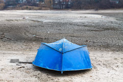 Old Upturned Boat Blue Lies on the Shore of the Dried Lake . Stock Photo