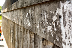 Old Urban Dirty Concrete Wall With Torn Worn Peeled Paper Poster, ADS. And Sticker Vertical Background Texture. Abstract Creative Surface royalty free stock photo