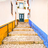 Old urban street and colorful facades in Obidos. Oeste, Leiria,. Old urban street in Obidos town. Colorful facades. Oeste region, Leiria district, Portugal Royalty Free Stock Photography