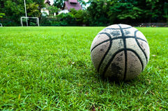 Old used ball on grass field Stock Photo