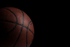 Old used basketball on black background. Studio shot of an used basketball on black background stock photography