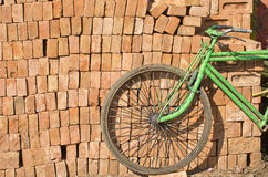 Old used bicycle near red bricks stack, India Royalty Free Stock Image