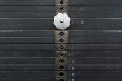 Old and used black weight stack with white numbers in a gym. Rusty flat metal weights. Fitness equipment Stock Photography