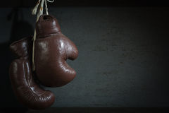 Old used boxing Gloves, hanging before a dirty Wall royalty free stock photos