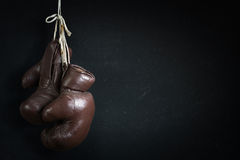 Old used boxing Gloves, hanging before a dirty Wall Stock Image