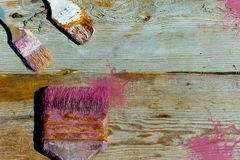 Old used brushes for paint on a wooden background. Repair, painting, renovation of interior. The place to advertise.  Stock Photo