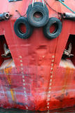 Old used car tires as fender on a shipboard. Red ship hull with Royalty Free Stock Photo