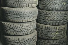 Old and used car tires. Background. Car tires in storage. Car tire recycling.  stock photos