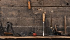 Old used carpenter tools on wood. Old carpenter tools on a wooden wall with space for text or image stock photo