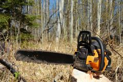 Old Used Chainsaw. A close up image of an old used chainsaw resting on a tree stump royalty free stock images