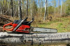 Old Used Chainsaw. A close up image of an old used chainsaw resting on a tree stump stock photo