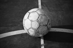 Old used football or soccer ball on cracked asphalt Royalty Free Stock Photo