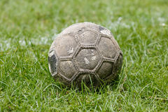 Old used football or soccer ball on field. Royalty Free Stock Photos