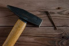 Old used hammer, wooden handle, metal head and rusty nail on wooden backdrop Royalty Free Stock Photos